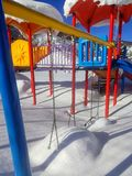 The swings are lonely in the snow royalty free stock image