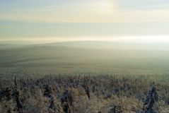 A frosty haze and a solar halo over the forest. Winter view from above on wooded hills in a frosty haze; in the corner of the picture a fragment of the solar Royalty Free Stock Image