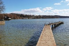 Wooden jetty on Ammersee lake. Winter view of Ammersee, Bavarian lake near Munich: coastline and wooden jetty full of mallards crouched on Royalty Free Stock Images