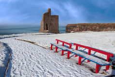 Winter view of ballybunion castle and red benches. A seasonal snow covered view of atlantic ocean and ballybunion castle with red benches on a frosty snow Royalty Free Stock Photos