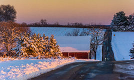 Winter view of a country road and red barn at sunset in rural Yo Stock Images