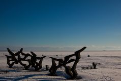 Winter view of empty beach covered with snow and concrete abstract sculpture. stock photo