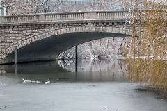 Winter view of a frozen river under a bridge Royalty Free Stock Photo
