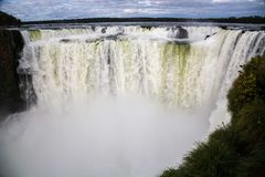 Winter view of Iguazu Falls Devil`s Throat under heavy clouds lead sky. Border of Brazil and Argentina. National Park. stock photo