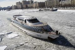 Winter view of the Moscow river embankment and cruise yacht sailing on iced water. Winter view of the Moscow river embankment. A Radisson royal luxury cruise stock image