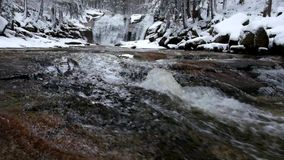 Winter view over foamy rapid stream into cascade of waterfall.Reflections of cloudy sky in water level. Deep freeze. stock video footage