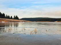 Winter view over frozen water level of lake, few boulders sticking out from the ice. Royalty Free Stock Photos