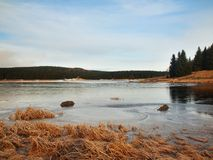 Winter view over frozen water level of lake, few boulders sticking out from the ice. Stock Photo
