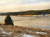 Winter view over lake with thin blue ice to opposite bank Royalty Free Stock Images