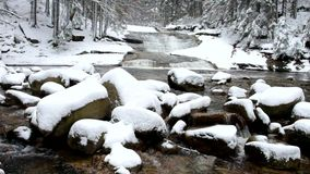 Winter view over snowy boulders to cascade of waterfall.Reflections of cloudy sky in water level.. Stream in deep freeze. stock video footage