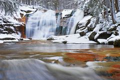 Winter view over snowy boulders to cascade of waterfall. Wavy water level.. Stream in deep freeze. Stock Photos