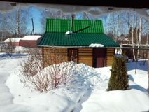 Winter view of a Russian banya from under the icicles of the living house Stock Images
