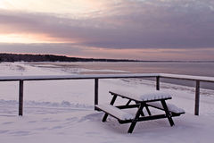 Winter view to the beach with a bench full of snow Stock Photography