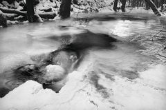 Winter view to frozen brook, icy twigs and icy boulders above rapid stream. Reflections of light in icicles. Black and white Royalty Free Stock Photo