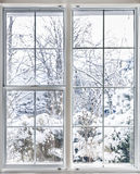 Winter view through window. Home vinyl insulated windows with winter view of snowy trees and plants stock photos