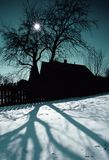 Winter Village. Winter scenery with tree, little rustic house and sun Stock Photo