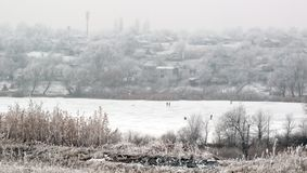 Winter village on coast river. In Ukraine royalty free stock photo
