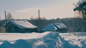 Winter village in a forest. Snow covered roofs of wooden houses stock footage