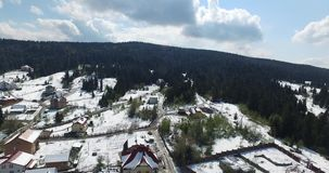 Winter. Village on a hill in the woods. Aerial view. Flying over the village in the hills of the valley, green forest in the mountains, roofs of houses and roads stock video