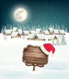 Winter village night background with wooden sign. Stock Photo