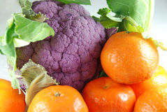 Winter vitamins. Colorful winter vitamins: purple cauliflower and orange clementines Royalty Free Stock Photography