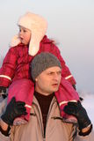 Winter walk. Child wering fur cap on a winter walk with her father Royalty Free Stock Photos