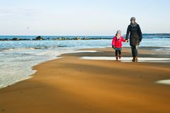 Winter walk by Baltic sea, mother and daughter royalty free stock photo