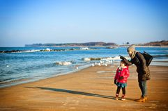 Winter walk by Baltic sea, mother and daughter Stock Photo