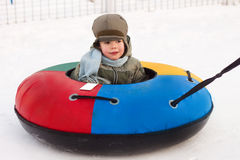 Winter walk, boy rides a Snow-tubing. Winter walk; boy rides a Snow-tubing; sleds; hill; playing snowballs Royalty Free Stock Images
