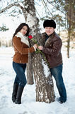 Winter walk of man and girl. Young people on a walk near a birch Royalty Free Stock Images
