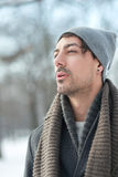 Winter walk. Otside portrait of young handsome man walking on snowy streets Royalty Free Stock Images