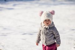 Winter walking of baby. Little girl is walking at the snowy park in cold sunny winter day Stock Photos