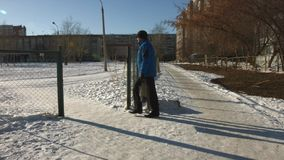 Winter. Walking man. A man in a blue jacket with the package goes on a snow-covered track stock footage