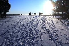 Winter Walking People. As the sun rose on January 1, a group of people hiked toward the sun leaving their tracks in the white snow. The blue sky gives a cold Royalty Free Stock Image