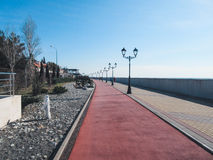 Winter walkway along the sea on a sunny day Royalty Free Stock Photo