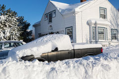 Winter Wallop. Piles of snow bury a truck and home in a North American suburb Stock Photos