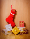 Winter warm sock with christmas gifts on wooden background Stock Images