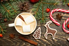 Winter warming sweet drink hot latte with marshmallows and cocoa in a mug with a Christmas holiday candy cane on a wooden backgrou royalty free stock image