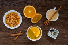 Winter warming tea and ingredients. Cup of tea, orange, sea buckthorn, honey and cinnamon on wooden table. anti-cold products. Top view Stock Images