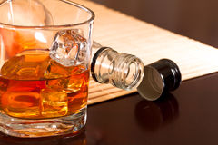 Winter warming whiskey. A glass of whiskey with ice and a bottle on the table Royalty Free Stock Photo
