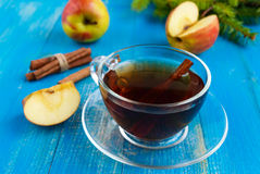 Winter warms festive Vitamin tea with apple and cinnamon on a blue wooden background. In a transparent cup of glass Royalty Free Stock Photo
