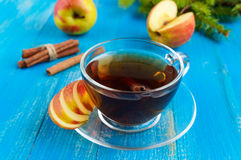 Winter warms festive Vitamin tea with apple. And cinnamon on a blue wooden background in a transparent cup of glass Royalty Free Stock Photos