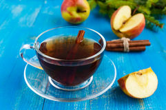 Winter warms festive Vitamin tea with apple and cinnamon on a blue wooden background. In a transparent cup of glass Royalty Free Stock Images