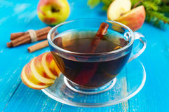 Winter warms festive Vitamin tea with apple and cinnamon on a blue wooden background. In a transparent cup of glass. Close up Stock Image