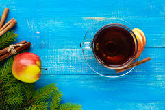 Winter warms festive Vitamin tea with apple and cinnamon on a blue wooden background in a transparent cup of glass. The top view Royalty Free Stock Photos