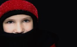 Winter Warmth. Girl in winter clothing on black background Stock Images