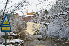 Winter in the waterfall. Snow-covered bushes, trees and factory buildings creates a great winter image Royalty Free Stock Photography