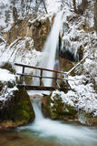 Winter Waterfall. Waterfall with icicles and snow around with a small wooden bridge on a winter day Stock Photos