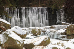 Winter waterfall in the Polish mountains. River and rocks covered with snow Stock Photography