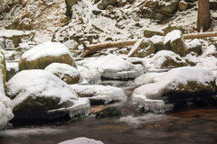 Winter waterfall in the Polish mountains. River and rocks covered with snow Royalty Free Stock Image